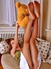 Red hot gal patting her plush toy with her yummy feet clad in tan pantyhose