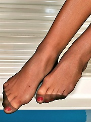Smashing gal demonstrating her delicious feet in black hose in the solarium