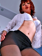 Playful redhead spreads her sexy pantyhosed hips