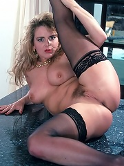 Big breasted blonde in black stockings spreads wide showing off her pussy