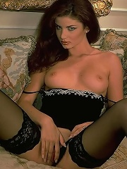 Gorgeous seductress in black stockings strips off clothes exposing hot body