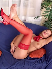 Redhead cutie in red stockings showing off her kickass body on the couch
